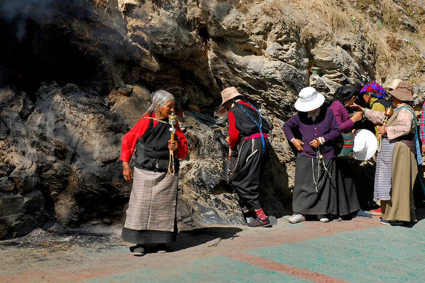 At a revered shrine, Tibetan Buddhist pilgrims wait their turn to practice an ancient Bon shamanistic ritual to the mountain deity of rubbing against the holy stones, worn smooth over the ages.  On the 8 km Lingkhora pilgrim circuit around the old city perimeter, Lhasa, Tibet.