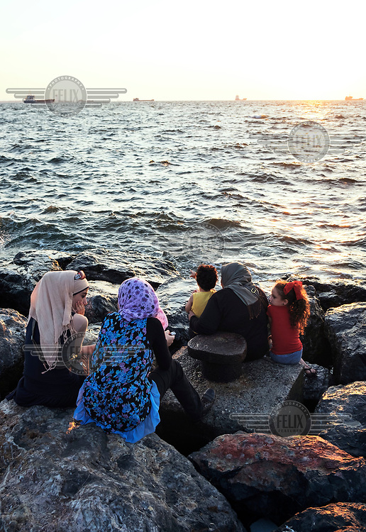 A family sits on the breakwater rocks beside the sea.