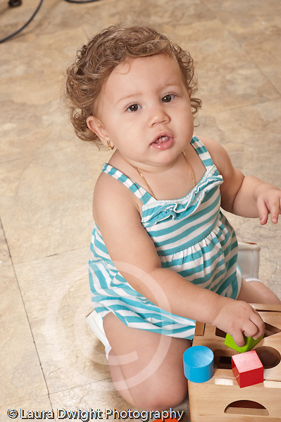 13 month old baby girl at home on floor playing with toy geometric shape sorter looking at camera vocalizing vertical