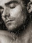 Sensual closeup portrait of a man face with closed eyes under pouring rain or shower water Black and white sepia toned Image © MaximImages, License at https://www.maximimages.com