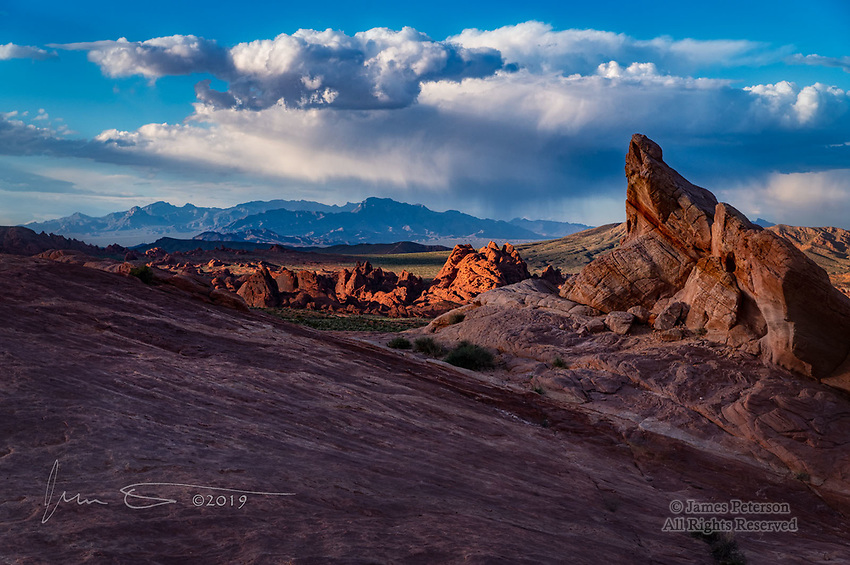 Moapa Peak Viewed from Valley of Fire, Nevada © 2019 James D Peterson.  Valley of Fire is one of the most remarkable landscapes on the planet.  This scene was captured shortly before sunset, when fleeting beams of warm-hued sunlight were breaking through the remnants of scattered rain showers.  The summit in the distance is Moapa peak in the Mormon Mountains.