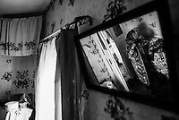 Typical belorussian house within exclusion zone - traditional decorations and clothes can be seen through the mirror hanging on the wall