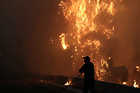 Pictured: A fireman battles with the flames.<br /> Re: A forest fire has been raging in the area of Kalamos, 20 miles east of Athens in Greece. There have been power cuts, country houses burned and children camps evacuated from the area.