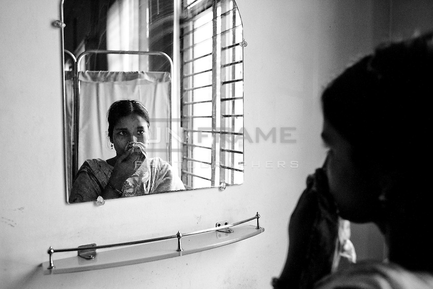 Rikta looking herself in the mirror. Rikta had her right arm amputated inside the rubble when she was rescued nearly 72 hours after the building collapsed, Savar, Dhaka.