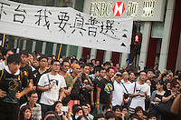 Pro-democracy protesters are seen listening to speeches in the middle of an interesction controlled by activists in Mong Kok, on the second day of the mass civil disobedience campaign Occupy Hong Kong, Mong Kok, Kowloon, Hong Kong, China, 30 September 2014. The movement is also being dubbed the 'umbrella revolution' after the versatile umbrellas used to shield protesters from rain, sun - and police pepper spray.