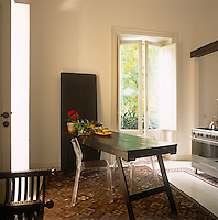 A modern kitchen diner with two transparent acrylic chairs and a trestle style table are placed on a patterned rug.