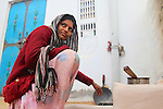 A woman prepares chai on an outdoor stove in a small village in Rajasthan.