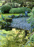 Heron sculptures reflected in upper pond of strolling pond garden (chisen kaiyu shiki niwa) in Portland Japanese Garden