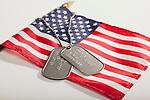 Studio shot of American flag and dog tags