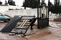 Pictured: A woman tries to get through the gates to the Mandra Cemetery that were damaged.<br /> Re: People have died, some still missing and severe damage caused by heavy rain and flash flooding in the area of Mandra, near Athens, Greece. Thursday 16 November 2017