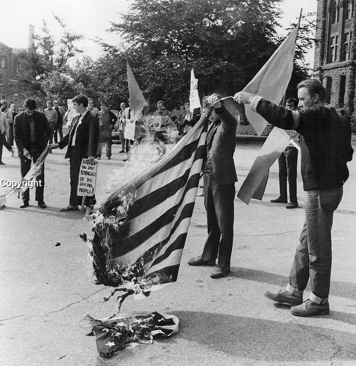 1969 FILE PHOTO - ARCHIVES -<br /> <br /> Flag Burning protest: A Free Quebec demonstrator holds a burning U.S. flag outside legislature Sunday during a demonstration to back Quebec's struggle for liberation. Seven protesters were arrested after fights with police.<br /> <br /> 1969<br /> <br /> PHOTO :  Dick Darrell - Toronto Star Archives - AQP