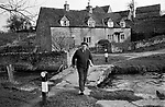 Mr Percy Howse delivering newspapers Sunday morning 1970s UK. Village life The Cotswolds. The River Eye footbridge. Lower and Upper Slaughter are twin villages on the River Eye and are know as The Slaughters.  1975
