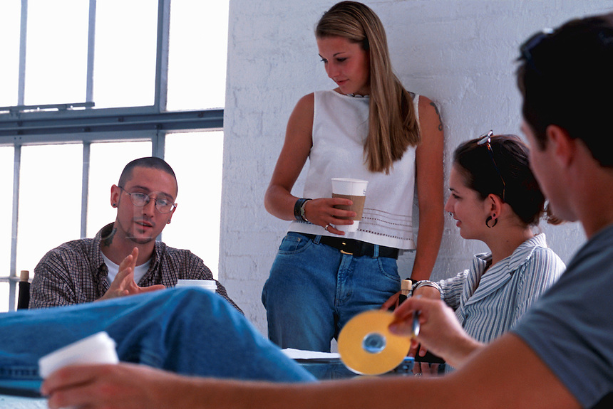 Young adults talk and work together as they hold a business meeting in a casual office setting.