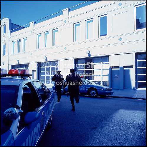 Policemen approaching white building