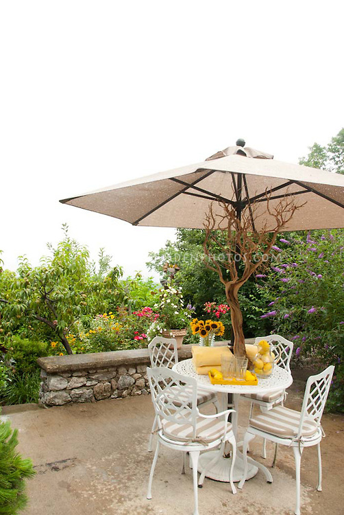 Dining table outside on patio, with white iron furniture, sunflowers, lemonade, glasses, large umbrella, flower garden for easy outdoor living