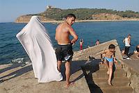 - Tunisia, bathing young people and veiled woman on waterfront of Tabarka town<br /> <br /> - Tunisia, giovani bagnanti e donna velata sul lungomare della città di Tabarka