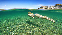 Woman swims at the bottom of an exotic beach on half underwater view