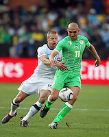 Rafik Djebbour of Algeria and Jay DeMerit of USA. USA defeated Algeria 1-0 in stoppage time in the 2010 FIFA World Cup at Loftus Versfeld Stadium in Pretoria, Sourth Africa, on June 23th, 2010.