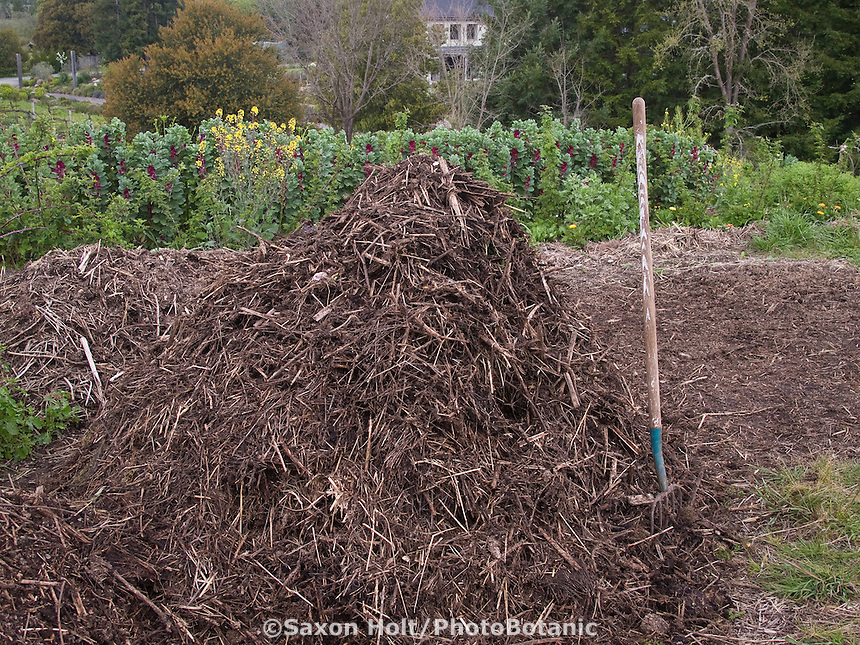 Compost pile with pitchfork by garden bed at Lynmar Estates