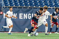 FOXBOROUGH, MA - AUGUST 7: Nicolas Firmino #29 of New England Revolution II dribbles as Wilfredo Rivera #62 of Orlando City B closely defends during a game between Orlando City B and New England Revolution II at Gillette Stadium on August 7, 2020 in Foxborough, Massachusetts.