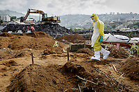 A burial, at the King Tom cemetery, of a person who is suspected to have died from ebola into one of a group of pre-dug graves. Due to the rapid increase in burials, caused by the ebola crisis, the cemetery is being enlarged and parts of a nearby rubbish dump is also being used to bury the dead.
