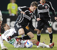DC United defender Bobby Boswell (32) is tackled by New England forward Clint Dempsey (2). The New England Revolution defeated DC United 2-1, Saturday, October 7, 2006, at RFK Stadium.