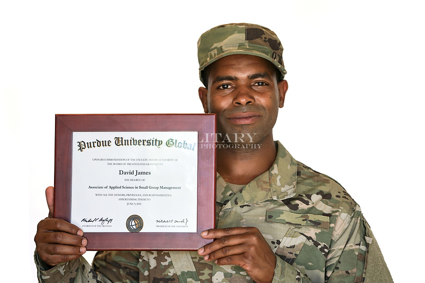 African American US military soldier in uniform in the studio with white background with diploma. For sale as stock photography, DOD compliant.