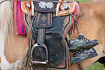 Children's tennis shoes hang from a mounted horse saddle, Mongolia