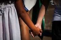 Two girls, children, one black and one white, two girls holding hands.