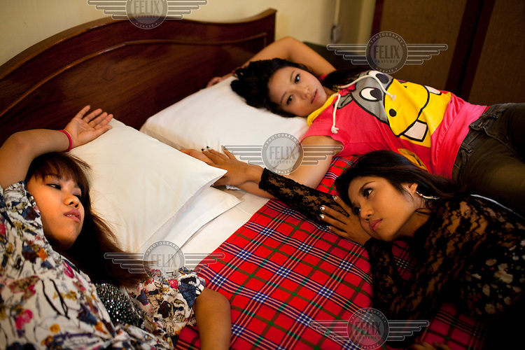 Kimmy (left) Cha Cha (centre) and Wai Hnin (right) all members of 'Me N Ma Girls', Myanmar's first girl band, lounge on a bed during a video shoot. The band's members were recruited by Australian dancer Nicole May. They sing and dance in the manner of many Western pop acts but in socially conservative Myanmar, they represent a radical break from the norm.