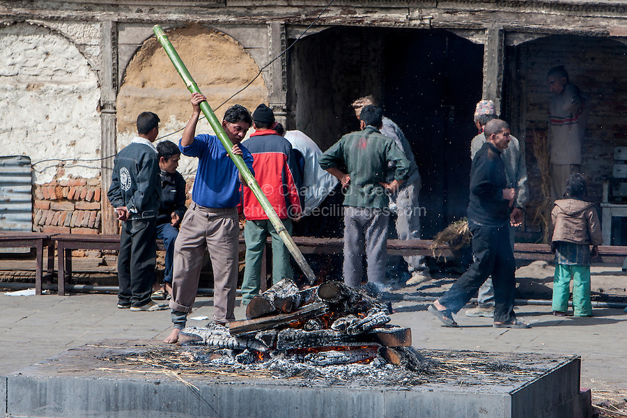 Nepal, Pashupatinath.  Cremation Stages.  Stiring the Remains after Several Hours of Cremation.
