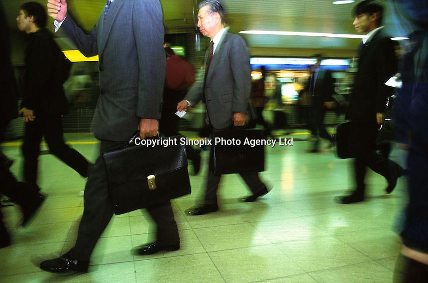 BUSINESS: TRANSPORT: JAPAN.Businessmen walking in rush at the train station in Japan...Photo by Richard Jones/sinopix.©sinopix