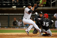 Birmingham Barons relief pitcher Mauricio Cabrera (22) covers home plate as Alfredo Rodriguez (35) slides in safely with umpire Matthew Brown looking on to make the call during a Southern League game against the Chattanooga Lookouts on May 1, 2019 at Regions Field in Birmingham, Alabama.  Chattanooga defeated Birmingham 5-0.  (Mike Janes/Four Seam Images)