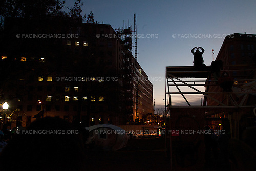 """Washington, D.C.<br /> December 4, 2011<br /> <br /> A lone protester awaits to be arrested as he sat on top of the wooden building Occupy D.C. constructed in McPherson Square. 31 protestors were arrested that day.<br /> <br /> Summary: OccupyD.C.'s overnight construction of a large wooden structure in McPherson Square ended two months of relatively peaceful coexistence with the U.S. Park Police, who said that the building appeared to be a permanent structure and was therefore illegal. Occupy D.C. said that they were building it to protect themselves from increasingly cold weather. Protesters defied repeated orders to abandon the building and take it down âEUR"""" setting the stage for a day long standoff âEUR"""" which ended in 31 arrests and the destruction of the building by the Park Police."""