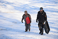 Andrew Newton (right) of Prairie Grove walks Friday, Feb. 19, 2021, back to the top of the hill alongside his son, David Newton, 10, while sledding at Battlefield State Park in Prairie Grove. The Newtons were taking a break from virtual instruction to take advantage of the good sledding conditions before warm temperatures melted the snow from the hillside. Visit nwaonline.com/210220Daily/ for today's photo gallery. <br /> (NWA Democrat-Gazette/Andy Shupe)