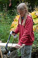Mädchen baut einen Vogel-Nistkasten aus Brettern, 2. Schritt: Bretter zusägen