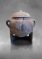 Hittite terra cotta cooking pot with perforated lid on a charcoal burner pot stand. Hittite Empire, Alaca Hoyuk, 1450 - 1200 BC. Çorum Archaeological Museum, Corum, Turkey. Against a grey bacground.