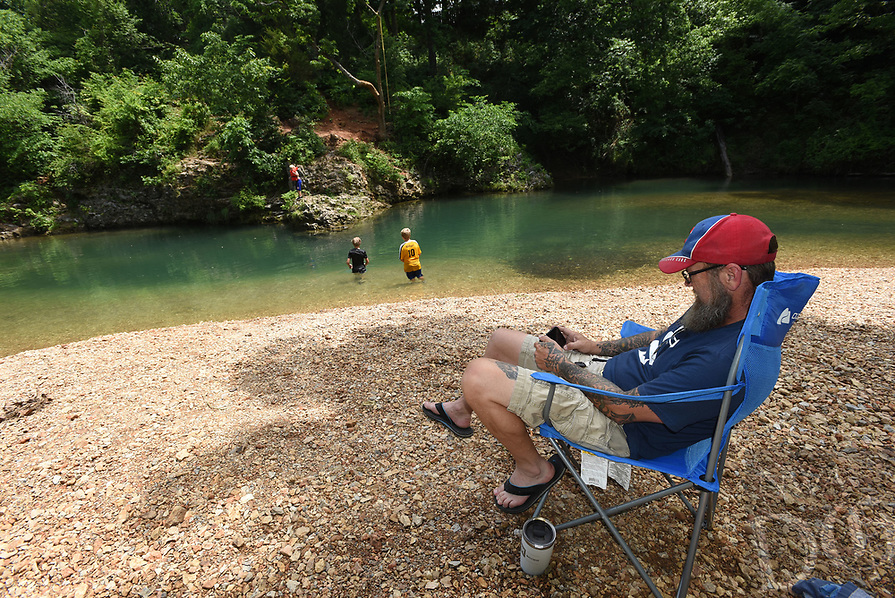 DOWN AT THE SWIMMING HOLE<br />Ryan Neil of Bentonville plays a game while watching his kids swim on Tuesday June 8 2021 at the McKissic Creek swimming hole along Wishing Spring Road in Bentonville. Wishing Spring flows into the creek creating cool, clear-water conditions at the popular swimming hole. Go to nwaonline.com/210609Daily/ to see more photos.<br />(NWA Democrat-Gazette/Flip Putthoff)