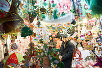 November 27, 2015, Yiwu China - Potential customers examine cheap Christmas decorations inside  a booth in the Festival Arts section of the Yiwu International Trade Market. Yiwu International Trade Market is the world's largest whole sale market for small commodities. Christmas decorations are available for bulk purchase all the year round.Photo by Dave Tacon / Sinopix