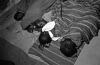 Children huddled together on the veranda at St. MaryÕs Hospital. The hospital is one of the few places children, known as Night Commuters, can find protection every  night to avoid being abducted by the Lords Resistance Army (LRA) in Northern Uganda. The LRA is primarily made up of abducted youth. Night Commuters find much more than safety in the compounds, they also find friendships, activity and fellowship. Tens of thousands of children, on average, make this exodus every evening. The war in Northern Uganda has been transpiring for two decades. Lachor, Gulu District, Uganda, Africa. July 2004 © Stephen Blake Farrington
