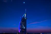 Colorful twilight over the iconic Burj Al Arab hotel, under a beautiful moon, from Jumeirah beach, in Dubai, United Arab Emirates, Asia
