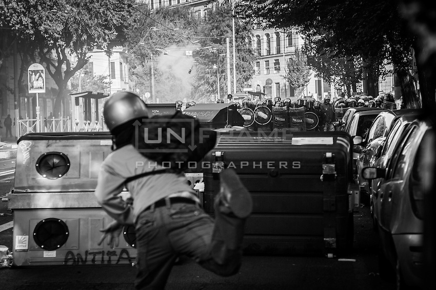 A rioter throws a bottle against the riot police  during the urban guerilla triggered by black blocs fringes. Rome, Italy. 15/10/2011