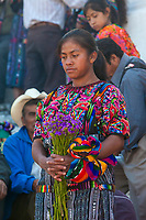 Chichicastenango, Guatemala.  Incense Surrounds Young  Quiche (Kiche, K'iche') Woman Standing on the Steps of Santo Thomas Church, Sunday Morning.