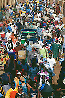 Gambia. Barra. Ferry on the Atlantic ocean. A white western tourist woman among a crowd of black people. Cars and people just arrived from a ferry ride. Women and men carry bags on their heads . © 2000 Didier Ruef