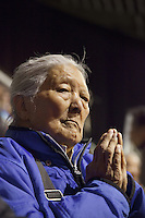 """Switzerland. Basel. St. Jakobshalle. An elderly woman prays during the Buddhist ritual. Avalokiteshvara (Chenresig in tibetan) particularly embodies compassion of a Buddha indiscriminately directed to all sentient beings. Avalokiteśvara is a bodhisattva who embodies the compassion of all Buddhas. Avalokiteśvara is one of the more widely revered bodhisattvas in mainstream Mahayana Buddhism, as well as unofficially in Theravada Buddhism. 8.02.2015 © 2015 Didier Ruef<br /> <br /> <br /> <br /> The 14th and current Dalai Lama is Tenzin Gyatso, recognized since 1950. He is the current Dalai Lama, as well as the longest-lived incumbent, well known for his lifelong advocacy for Tibetans inside and outside Tibet. Dalai Lamas are amongst the head monks of the Gelug school, the newest of the schools of Tibetan Buddhism. The Dalai Lama, also called """" Ocean of Wisdom"""" is considered as the incarnation of Chenresi, the Bodhisattva of compassion who is also the protective deity of Tibet. 7.02.2015 © 2015 Didier Ruef"""