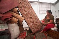 A woman reads newspaper sitting inside of her tent. Shanku, near Kathmandu, Nepal. May 9, 2015