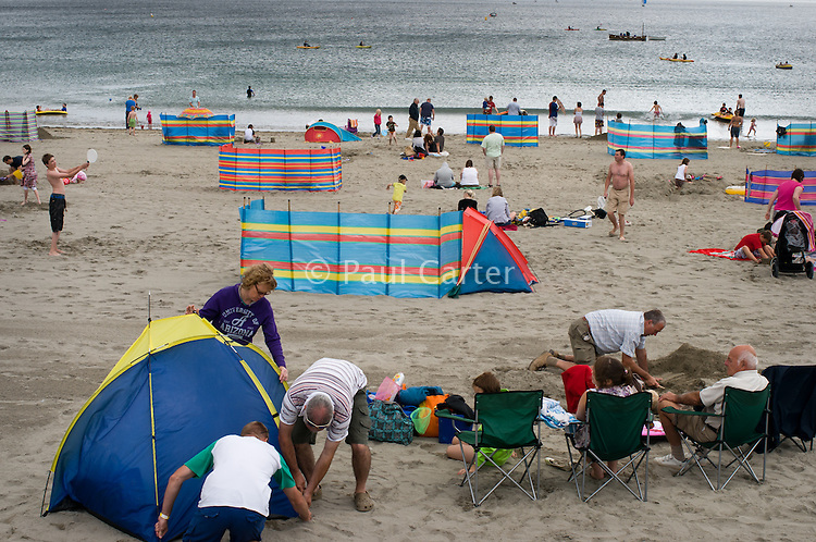 Group of men putting up a beach shelter on Looe beach on an overcast day with the sea in the background. Looe, Cornwall, UK
