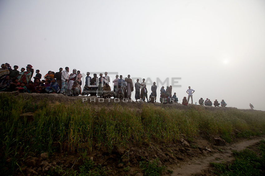 Bangladeshi people gather on the banks of the River Padma where a passenger ferry capsized Sunday, Paturia , in Manikganj district, about 80 kilometers northwest of Dhaka, Bangladesh. Feb. 23, 2015.