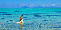 Young Polynesian fisherman in the lagoon with his fishing net on Huahine island, Pacific Ocean, with Raiatea and Taha'a islands in the background