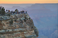 Late day sun bathes the precipitous gorge and its lilliputian sized visitors at the Grand Canyon.